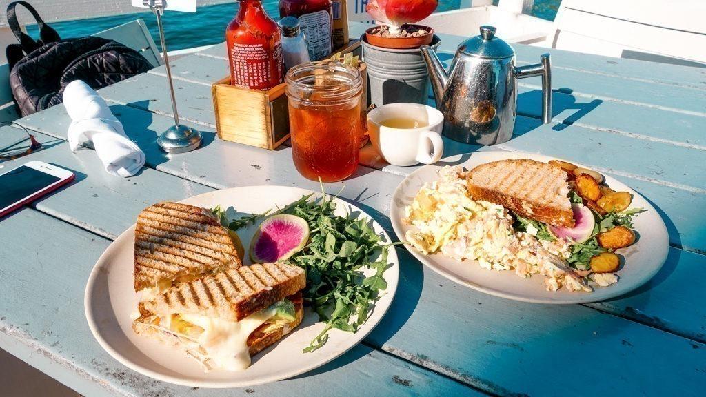 Dois pratos, um é um sanduíche e o outro são ovos com salmão.
